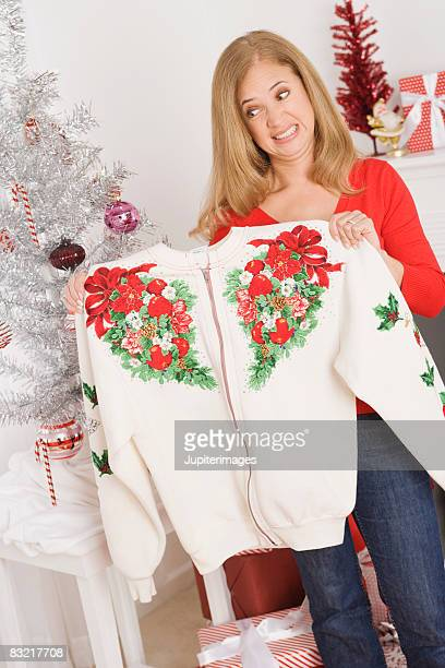 Cringing woman holding sweater she got for Christmas