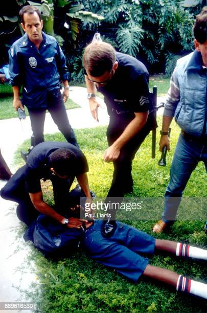 A Crip dressed in blue showing the Gang colors is arrested by the Los Angeles Police Department anti gang unit with two friends after stealing a...
