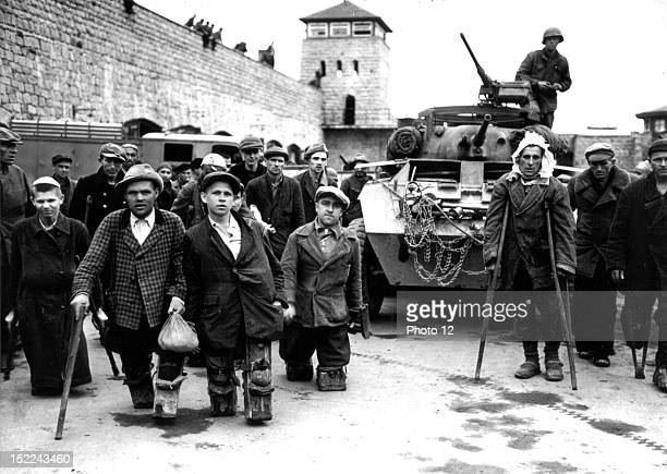 Crippled Russian and Polish prisoners in front of an armored car of the 11th Armored Division 3rd US Army in the Mauthausen Concentration camp 1945