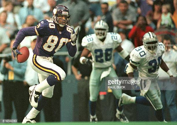 Cris Carter of the Minnesota Vikings runs away from Dallas Cowboys defenders Darren Woodson and Kenny Wheaton en route to a 54 yard touchdown...