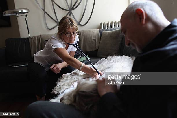 Cris Cristofaro holds his dog Dino as veterinarian Wendy McCulloch checks his heartbeat after performing an inhome euthanasia on May 9 2012 in New...