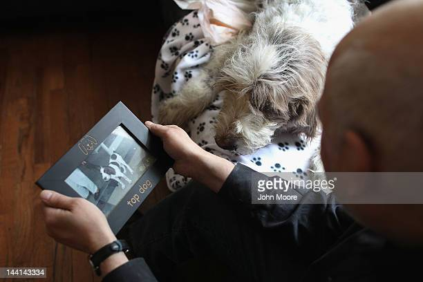 Cris Cristofaro looks over a puppy photo of his dog Dino as veterinarian Wendy McCulloch prepares to perform an inhome pet euthanasia on the...