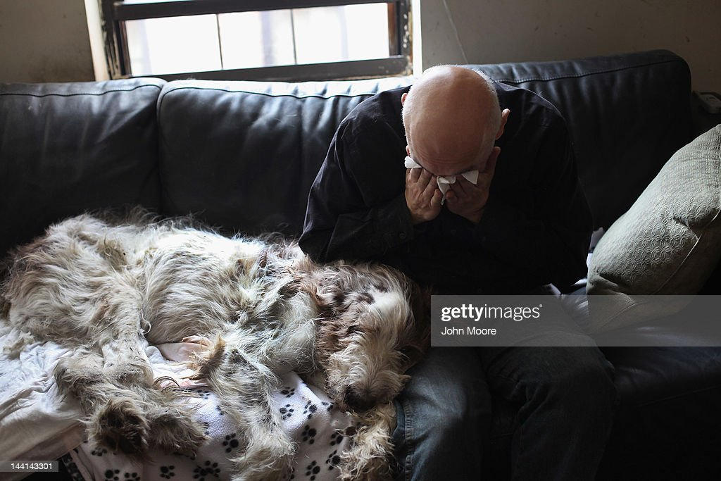Cris Cristofaro weeps over his dog Dino after veterinarian Wendy McCulloch euthanized the 12-year-old Italian Spinone on May 9, 2012 in New York City. Cristofaro, a New York City artist, made the difficult decision to end Dino's life when oral cancer became unbearable for the dog. End of life issues have become increasingly important for pet owners, as advanced medical treatments and improved nutrition are extending pets lives well into old age. McCulloch runs Pet Requiem, a home veterinary service designed to provide geriatric care and in-home euthanasia for dying pets in the New York and New Jersey area. Many pet owners are choosing such in-home care to try and provide a humane and compassionate 'good death' for their beloved pets.