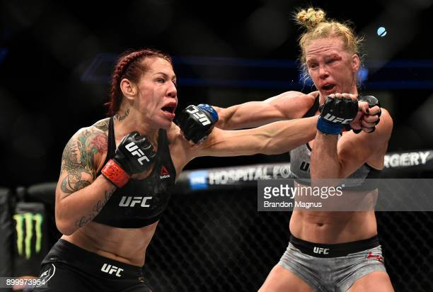 Cris Cyborg of Brazil and Holly Holm trade punches in their women's featherweight bout during the UFC 219 event inside TMobile Arena on December 30...