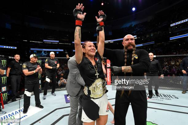 Cris Cyborg of Brazil receives the championship belt from UFC President Dana White after defeating Tonya Evinger in their UFC women's featherweight...