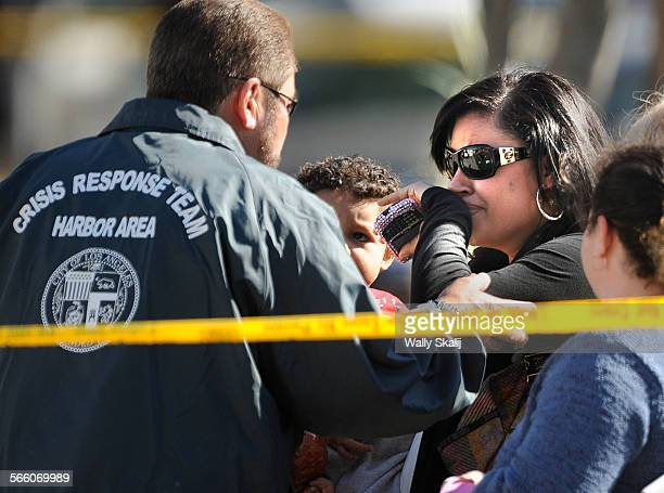 Crisis Response Team help an unidentified woman outside the home where 7 people were found dead including five children in WIlmington Tuesday