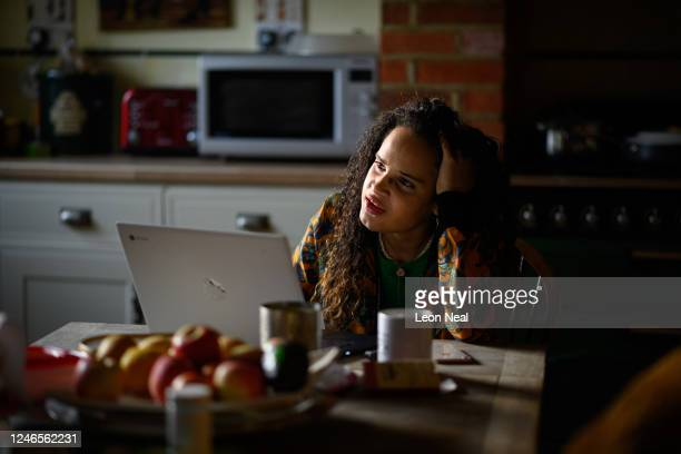 Crisis Volunteer and Coach Lauren Duncan sits with her laptop in the kitchen where she usually logs on for her shifts with the crisis text service...