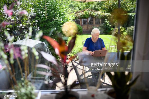 Crisis Volunteer Sheila Angel sits in the garden with the laptop she uses for her work with the crisis text service Shout 85258 on June 02 2020 in...