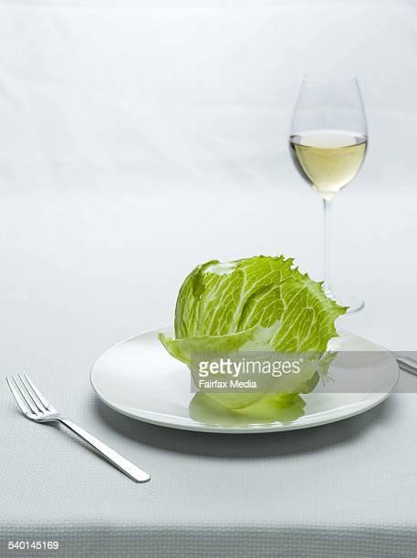 A crisp iceberg lettuce leaf balances on a white dinner plate accompanied by a glass of white wine 30 January 2007