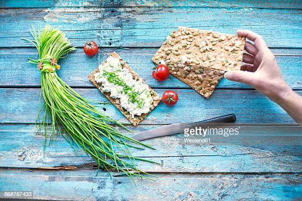Crispbread, cream cheese, bunch of chive, cocktail tomatos and knife, hand taking crispbread
