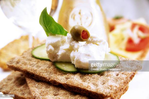 Crispbread with cheese and olive, close-up
