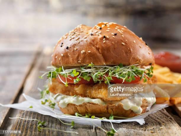 hambúrguer de peixe crocante com molho de tarter, alface, tomate em um bolo de brioche - sanduíche - fotografias e filmes do acervo
