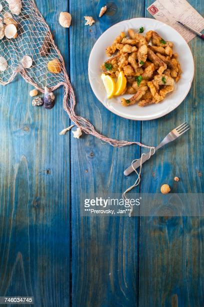 Crispy fish fingers on a blue wooden surface with maritime decorations