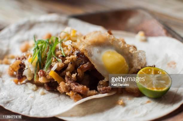 crispy pork chicharrones and fried quail egg flour tortilla - chicharrones fotografías e imágenes de stock