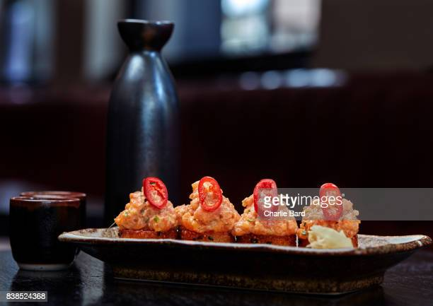 crispy sushi with saki on a table - sushi restaurant stock photos and pictures
