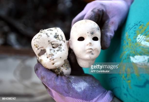 Crista Gatti holds a pair of dolls she made that she found in the rubble of her burned home in the Coffey Park area of Santa Rosa California on...