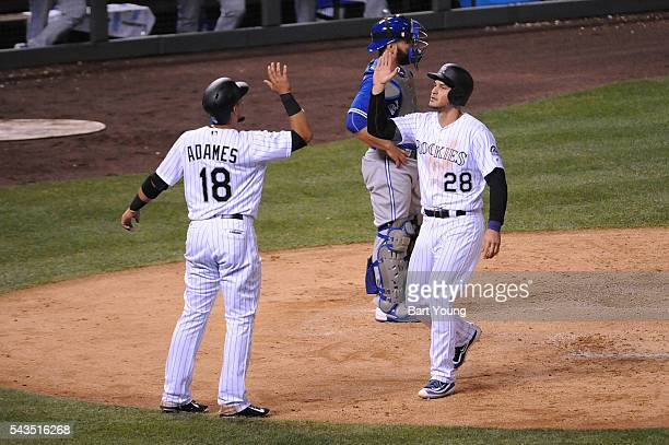 Cristhian Adames and Nolan Arenado of the Colorado Rockies celebrate runs in the fourth inning against the Toronto Blue Jays at Coors Field on June...