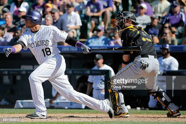 Cristhian Adames of the Colorado Rockies takes an at bat as catcher Chris Stewart of the Pittsburgh Pirates backs up the plate at Coors Field on...