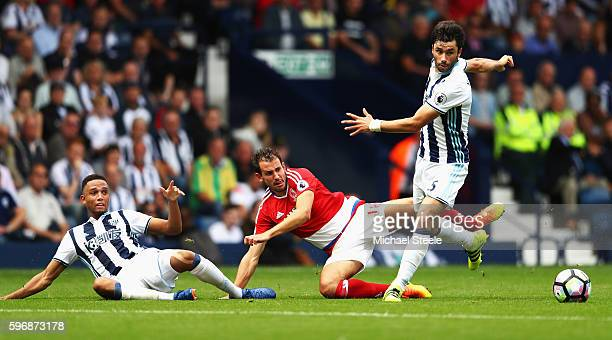 Cristhian Stuani of Middlesbrough is challenged by Brendan Galloway and Claudio Yacob of West Bromwich Albion during the Premier League match between...