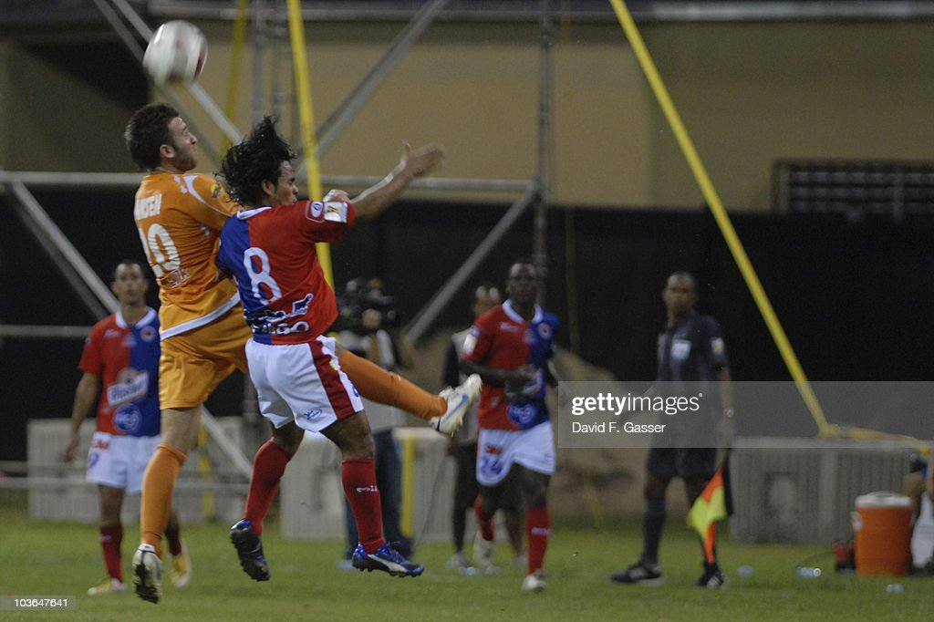 Cristian Alvarez of FAS vie for the ball with Joshua Hansen of Islanders during their match as part of 2010 CONCACAg Champions League at Juan Ramon Loubriel Stadium on August 25, 2010 in Baymon, Puerto Rico.