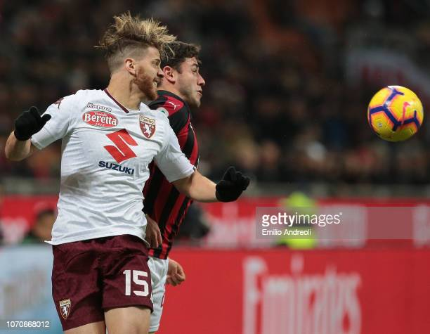 Cristian Ansaldi of Torino FC jumps for the ball against Davide Calabria of AC Milan during the Serie A match between AC Milan and Torino FC at...