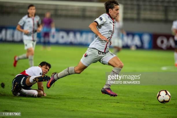 Cristian Bernardi of Argentina's Colon de Santa Fe dribbles past Carlos Flores of Peru's Deportivo Municipal during their Sudamericana Cup football...