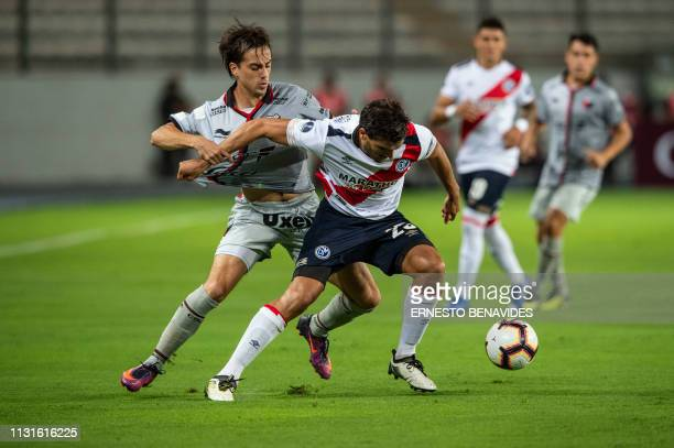 Cristian Bernardi of Argentina's Colon de Santa Fe vies for the ball with Alvaro Ampuero of Peru's Deportivo Municipal during their Sudamericana Cup...