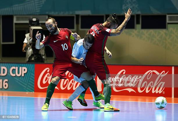 Cristian Borruto of Argentina battles with Ricardinho of Portugal and Joao Matos of Portugal during the FIFA Futsal World Cup semifinal match between...