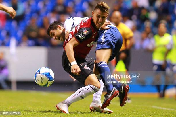 Cristian Calderon of Atlas battles for the ball against Alonso Zamora of Puebla during the 6th round match between Puebla and Atlas as part of the...