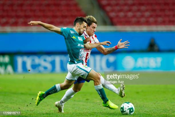 Cristian Calderon of Chivas fights for the ball with Fernando Navarro of Leon during the semifinal first leg match between Chivas and Leon as part of...