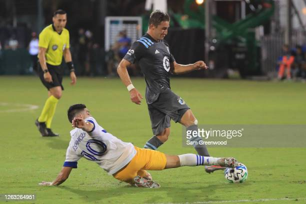 Cristian Espinoza of San Jose Earthquakes slides for the ball against Ethan Finlay of Minnesota United during a quarter final match of MLS Is Back...