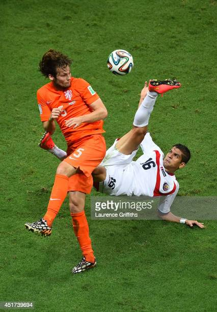 Cristian Gamboa of Costa Rica attempts a clearance against Daley Blind of the Netherlands during the 2014 FIFA World Cup Brazil Quarter Final match...