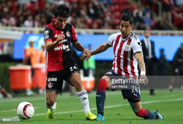Cristian Gonzalez of Atlas fights for the ball with Carlos Cisneros of Chivas during the round of sixteen match between Chivas and Atlas as part of...