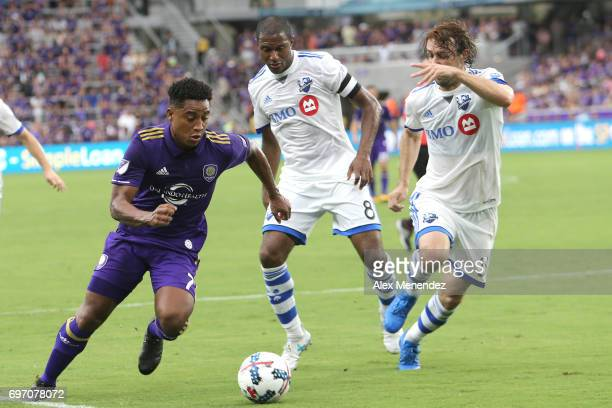 ORLANDO FL JUNE 17 Cristian Higuita of Orlando City SC runs past Patrice Bernier of Montreal Impact and Marco Donadel of Montreal Impact during a MLS...