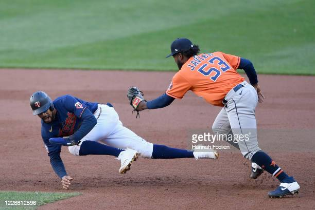 Cristian Javier of the Houston Astros tags out Byron Buxton of the Minnesota Twins after Buxton was caught off first base during the eighth inning of...