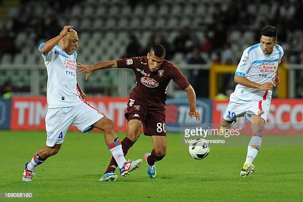 Cristian Jonathas of Torino FC in action against Sergio Bernardo Almiron and Lucas Nahuel Castro of Calcio Catania during the Serie A match between...