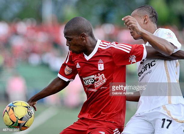 Cristian Lasso of America struggles for the ball with Harrison Canchimbo of Llaneros FC during a match between America de Cali and Llaneros FC as...