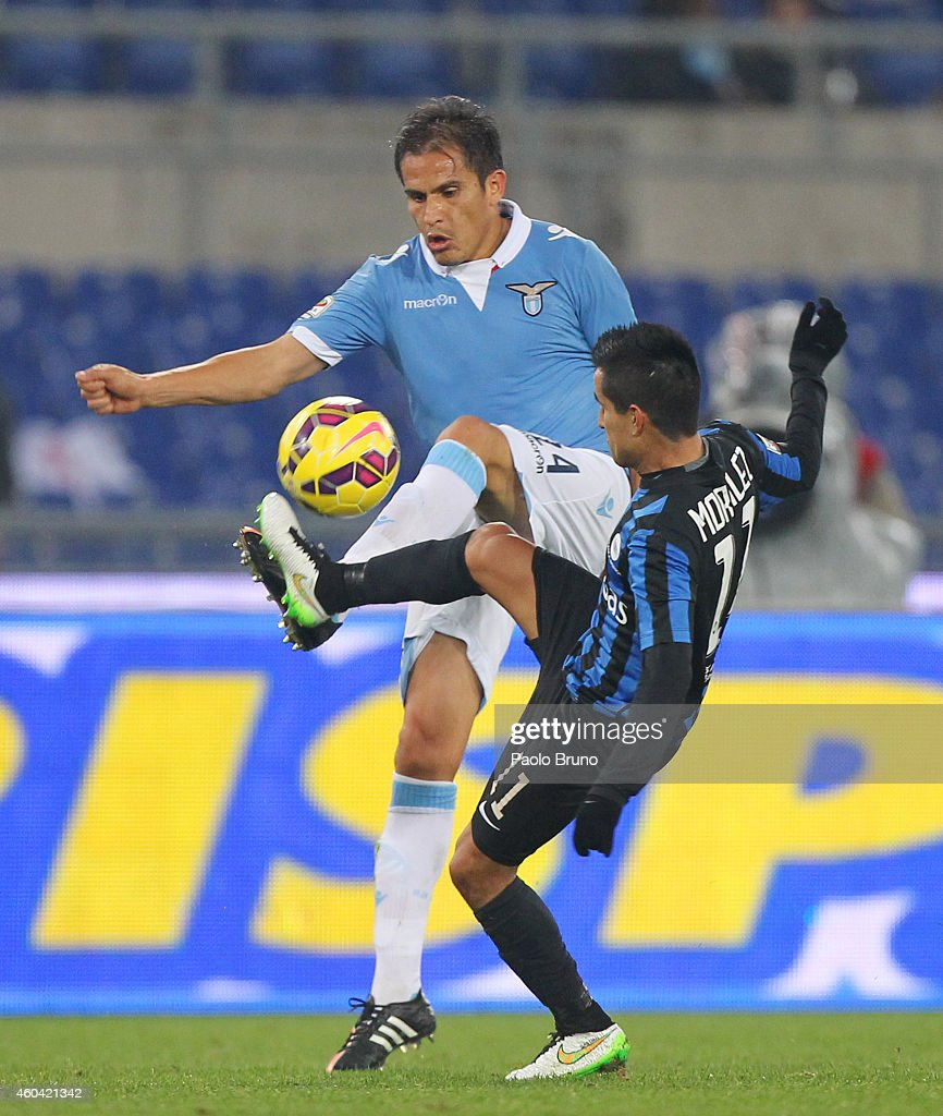 Cristian Ledesma (L) of SS Lazio competes for the ball with Maximiliano Moralez of Atalanta BC during the Serie A match between SS Lazio and Atalanta BC at Stadio Olimpico on December 13, 2014 in Rome, Italy.