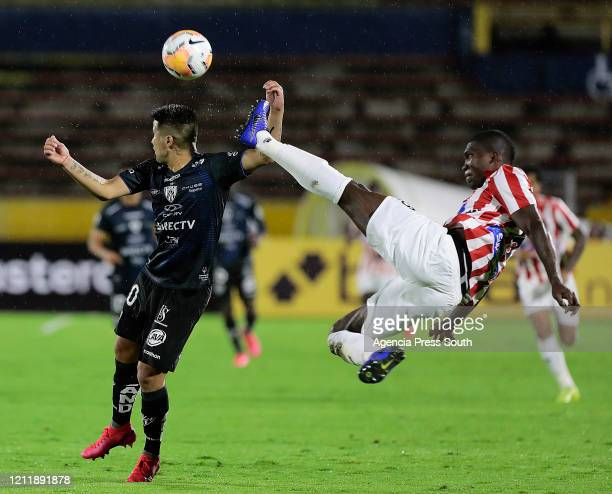Cristian Ortiz of Independiente del Valle fights for the ball with German Mera of Junior during a Group A match between Independiente del Valle and...