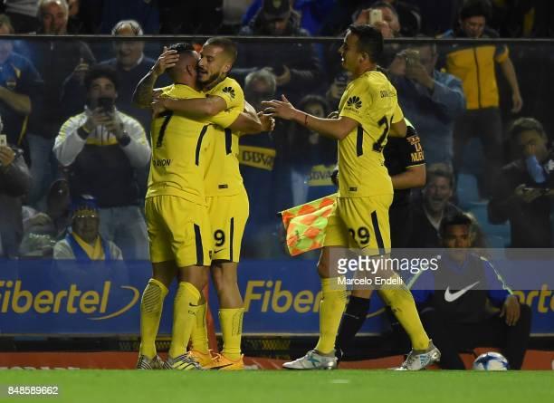 Cristian Pavon of Boca Juniors celebrates with teammates Dario Benedetto and Leonardo Jara after scoring the third goal of his team during a match...