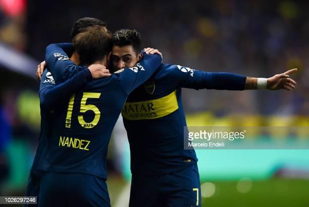 Cristian Pavon of Boca Juniors celebrates with teammates Leonardo Jara and Nahitan Nández after scoring the first goal of his team during a match...