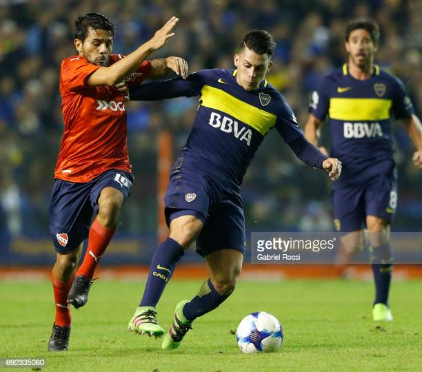 Cristian Pavon of Boca Juniors fights for the ball with Walter Erviti of Independiente during a match between Boca Juniors and Independiente as part...