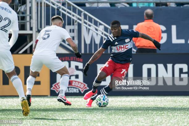 Cristian Penilla of New England Revolution breaks left as Francisco Calvo of Chicago Fire defends during a game between Chicago Fire and New England...