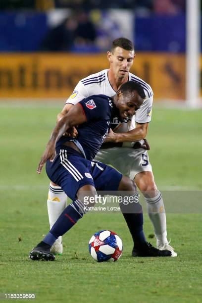 Cristian Penilla of New England Revolution struggles to block Daniel Steres of Los Angeles Galaxy during a game at Dignity Health Sports Park on June...