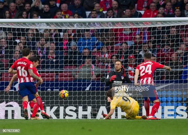 Cristian 'Portu' Portugues of Gerona beats Jan Oblak of Atletico de Madrid to score his team's opening goalduring the La Liga match between Atletico...