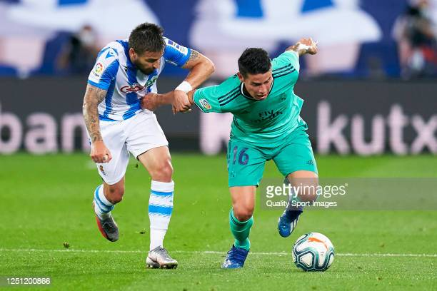Cristian Portugues 'Portu' of Real Sociedad competes for the ball with James Rodriguez of Real Madrid during the La Liga match between Real Sociedad...
