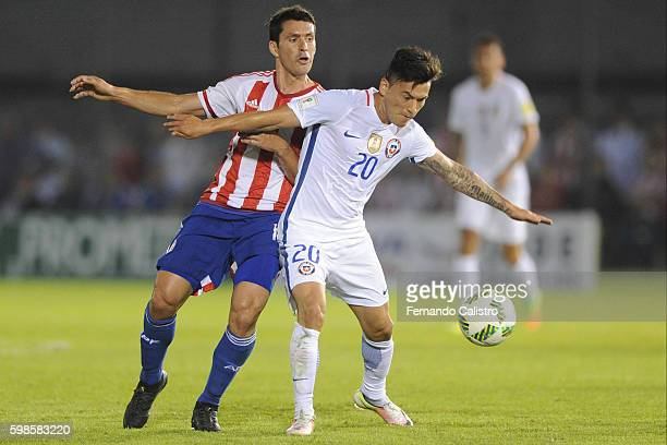 Cristian Riveros of Paraguay and Charles Aranguiz of Chile fight for the ball during a match between Paraguay and Chile as part of FIFA 2018 World...