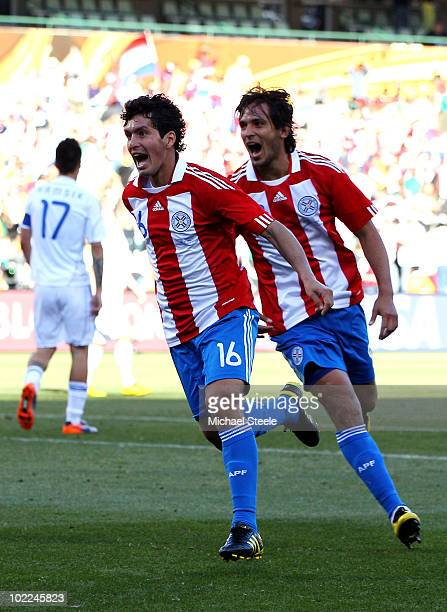 Cristian Riveros of Paraguay celebrates scoring his side's second goal with team mate Roque Santa Cruz during the 2010 FIFA World Cup South Africa...