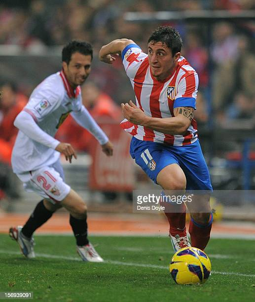 Cristian Rodriguez of Club Atletico de Madrid beats Cicinho of Sevilla FC during the La Liga match between Club Atletico de Madrid and Sevilla FC at...