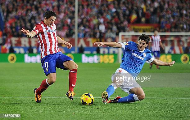 Cristian Rodriguez of Club Atletico de Madrid is tackled by Mikel San Jose of Athletic Club during the La Liga match between Club Atletico de Madrid...